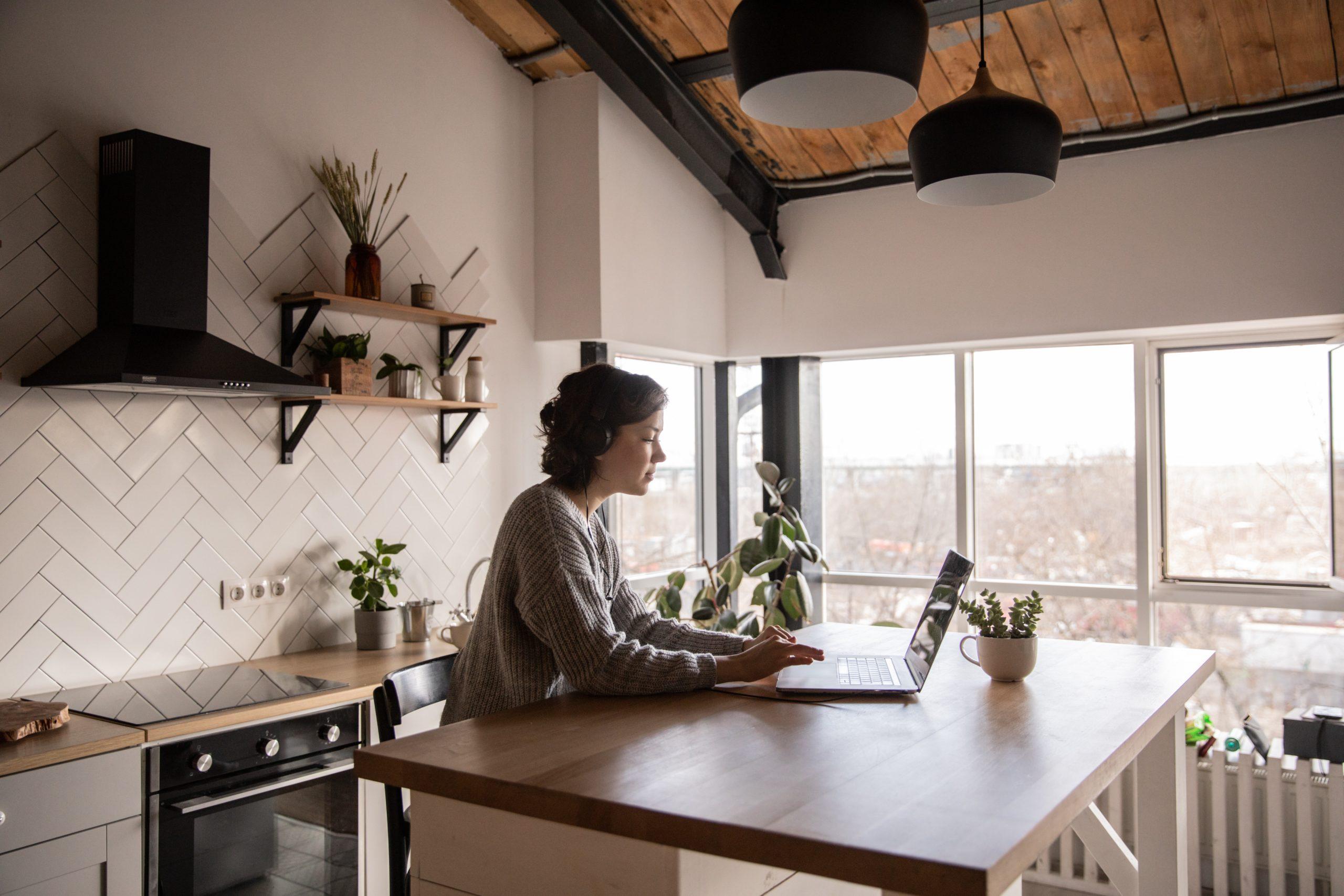 En ung kvinna sitter vid en köksö med en laptop