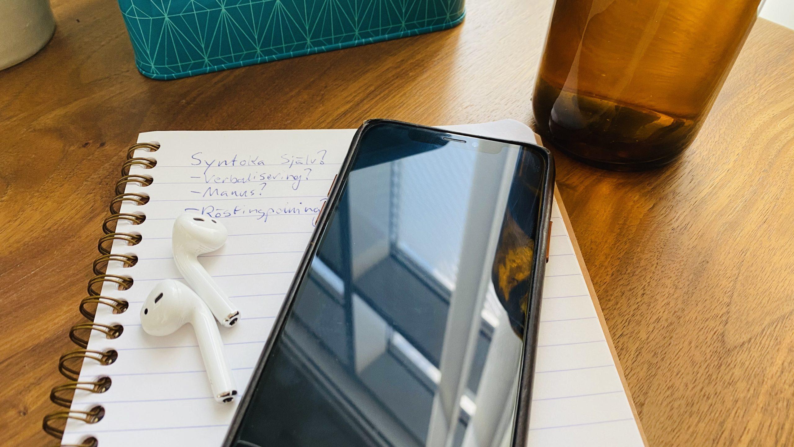 Foto på hörlurar och mobiltelefon på ett anteckningsblock